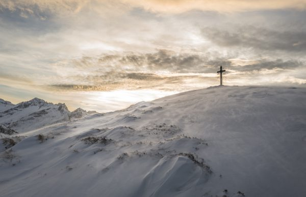 Snowy cliff with a cross at the top
